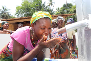 The Water Project: Kamasondo, Masinneh Village -  Woman Drinks From The Completed Well
