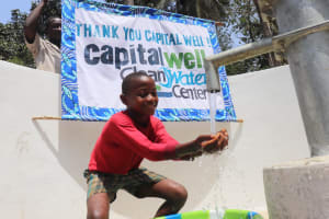 The Water Project: Lokomasama, Bompa Morie Village -  Kid At Well With Banner