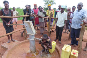 The Water Project: Rwenziramire Community -  Child Drinks From The Well