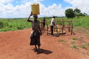 The Water Project: Rwenziramire Community -  Woman Carrying Water Collected At The Rehabilitated Well