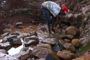 The Water Project: Shikoye Community, Kwa Witinga Spring -  Backfilling Large Stones