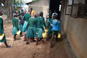 The Water Project: Mali Mali Primary School -  Pupils Taking Water To The Kitchen