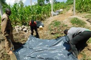 The Water Project: Shianda Community, Akhonya Spring -  Backfilling Plastic Sheet