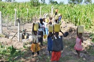 The Water Project: Shianda Community, Akhonya Spring -  Community Members Carry Water