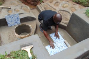 The Water Project: Lukala West Community, Luka Spring -  Fixing Of Tiles