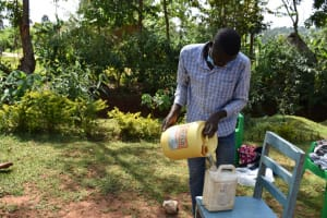 The Water Project: Lukala West Community, Luka Spring -  Filling The Leaky Tin With Water