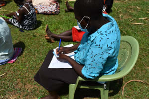 The Water Project: Lukala West Community, Angatia Spring -  Community Member Takes Notes