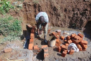 The Water Project: Shisasari Itumbu Community, Mathias Juma Spring -  Raising The Wall