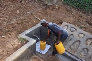 The Water Project: Shisasari Itumbu Community, Mathias Juma Spring -  Joseph Fetching Water