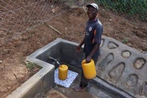 The Water Project: Shisasari Itumbu Community, Mathias Juma Spring -  Water User Fetching Water