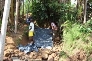 The Water Project: Shibikhwa Community, Musotsi Spring -  Backfilling With Plastic Sheet