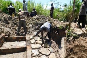 The Water Project: Shikokhwe Community, Mulika Spring -  Laying The Stones