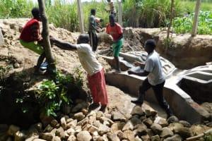 The Water Project: Shikokhwe Community, Mulika Spring -  Backfilling Stone