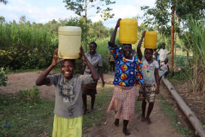 The Water Project: Shikokhwe Community, Mulika Spring -  Women Excited Carrying Water Home