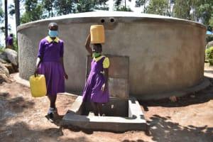 The Water Project: Kapsogoro Primary School -  Children Carrying Water