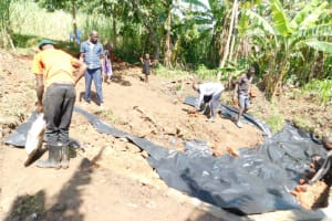 The Water Project: Eshimuli Community, Mbayi Spring -  Back Filling With Soil