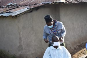 The Water Project: Eshimuli Community, Mbayi Spring -  Helping Mzee Fredrick Mask Up
