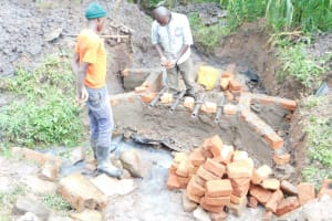 The Water Project: Eshimuli Community, Mbayi Spring -  Pipe Setting