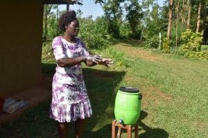 The Water Project: Mukhuyu Community, Namukuru Spring -  Trainer Joyce Shows Hand Washing