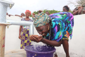 The Water Project: St. Peter Roman Catholic Primary School -  Community Member Drinks From The Well