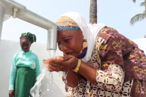 The Water Project: DEC Kitonki Primary School -  Teacher Drinks From The Well