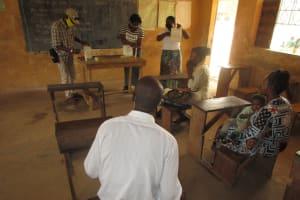 The Water Project: DEC Kitonki Primary School -  Teachers Constructing Tippy Tap