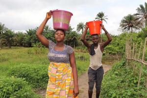 The Water Project: Kamasondo, Feradugu Village -  Community Members Carrying Water