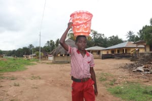 The Water Project: Lokomasama, Mapiterr, Al Kitab Primary School -  Student Carrying Water