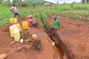 The Water Project: Isagara Primary School -  Collecting Water From Stream