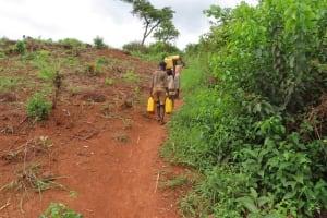 The Water Project: Kiryamasasa Community -  Carrying Water Uphill