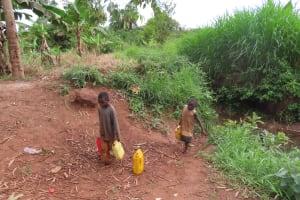 The Water Project: Kiryamasasa Community -  Children Hauling Water