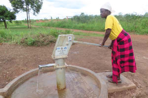 The Water Project: Nsamya Nusaff II Well -  Water Flowing