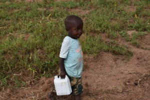 The Water Project: Chombeli Community, Ernest Kuta Spring -  Emmanuel Carrying Water