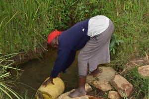 The Water Project: Chombeli Community, Ernest Kuta Spring -  Mama Rosa Fetching Water