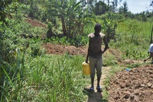 The Water Project: Muting'ong'o Community, Chivuyi Spring -  Emmanuel Carrying Water