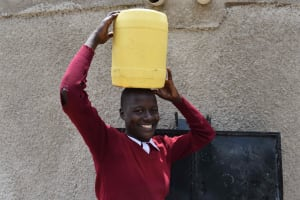 The Water Project: Gimariani Primary School -  Student Carrying Water