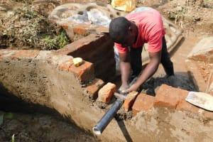 The Water Project: Nangurunya Community, Robert Musali Spring -  Pipe Setting
