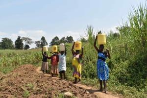 The Water Project: Nangurunya Community, Robert Musali Spring -  Community Carrying Water