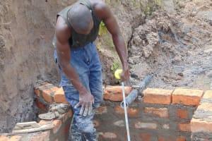 The Water Project: Shamoni Community, Shiundu Spring -  Pipe Setting