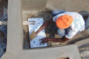The Water Project: Shamoni Community, Shiundu Spring -  Placing Tiles