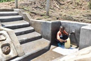 The Water Project: Shamoni Community, Laban Ang'ata Spring -  Ian Fetching Water