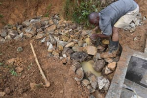 The Water Project: Mundoli Community, Pamela Atieno Spring -  Backfilling With Stones