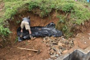 The Water Project: Mundoli Community, Pamela Atieno Spring -  Backfilling With Black Plastic