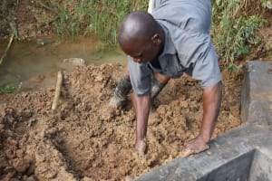 The Water Project: Mundoli Community, Pamela Atieno Spring -  Backfilling With Clay