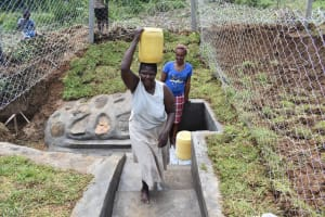The Water Project: Mundoli Community, Pamela Atieno Spring -  Florence Onganyo Fetching Water