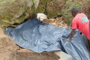The Water Project: Lunyinya Community, Makunga Spring -  Backfilling With Plastic