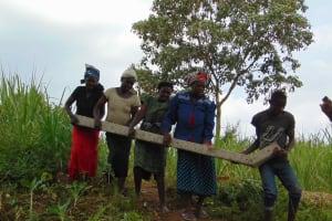 The Water Project: Malimali Community, Onyango Spring -  Community Members Assist