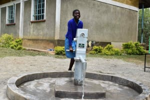 The Water Project: Bukhakunga Primary School -  A Pupil Happy To Pump Water From The Complete Borehole