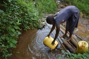 The Water Project: Mungakha Community, Mungakha Spring -  Caroline Filling Container