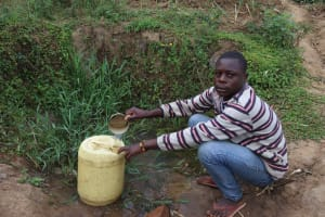 The Water Project: Makunga Community, Malaha Spring -  Shadrack Collecting Water